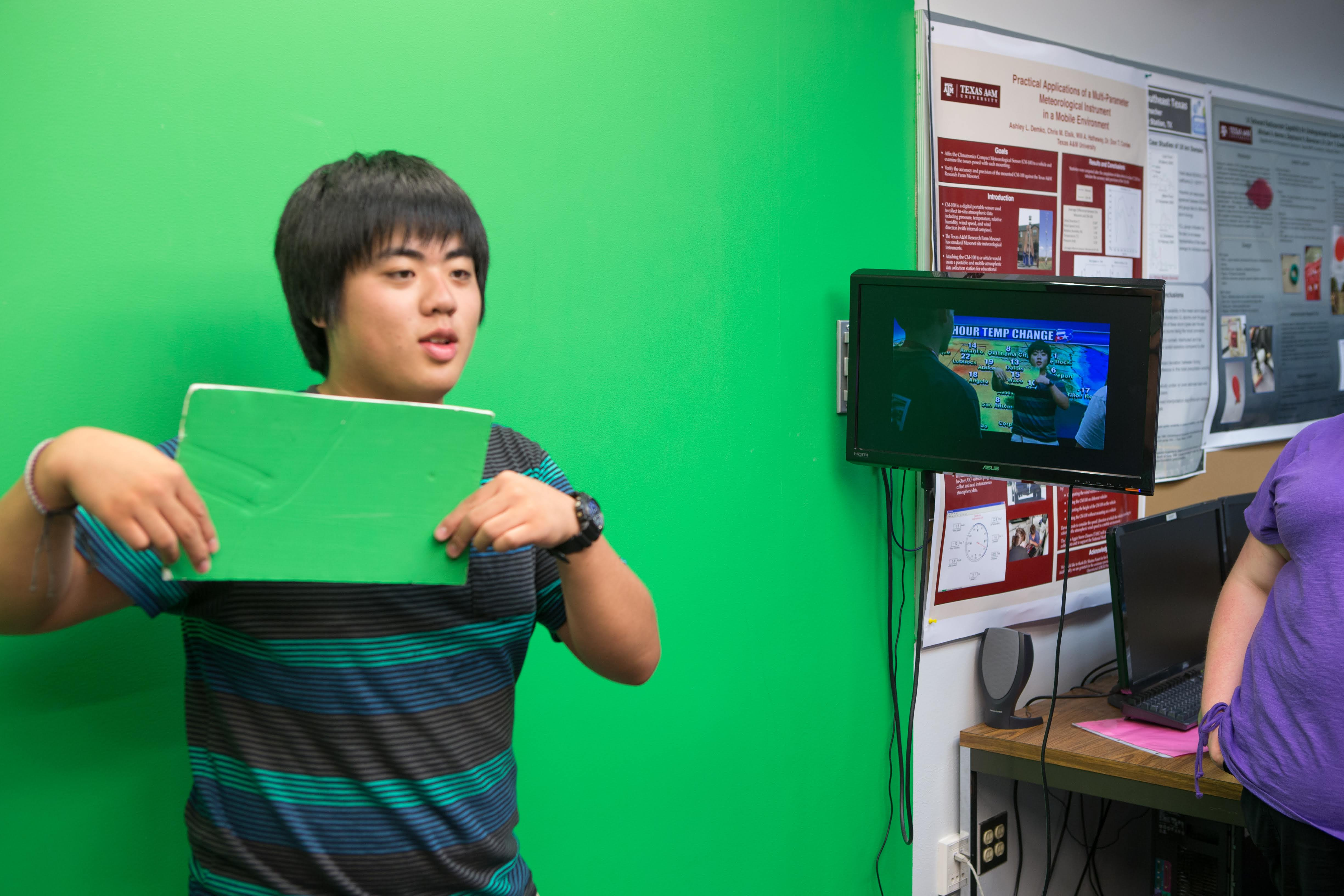 Student in front of green screen in the TV studio