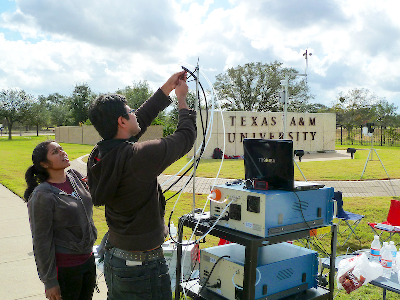 Graduate students taking air samples on campus